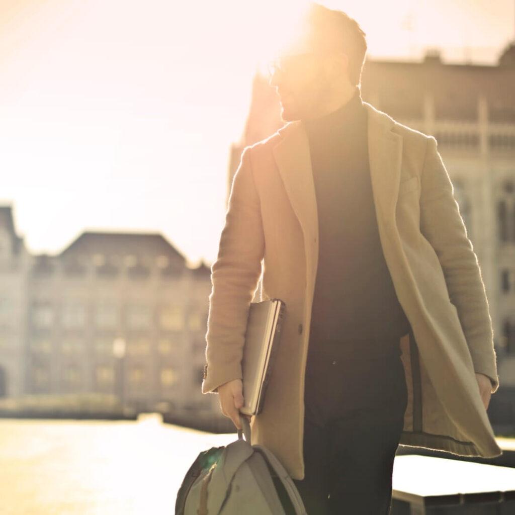 Hombre elegante sujetando una mochila en una plaza
