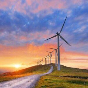 Monte con molinos de energía eólica y puesta de sol al fondo