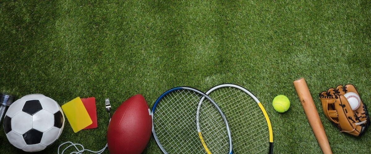 elementos deportivos como pelotas, raquetas, guantes, bate, etc... en fila sobre césped verde